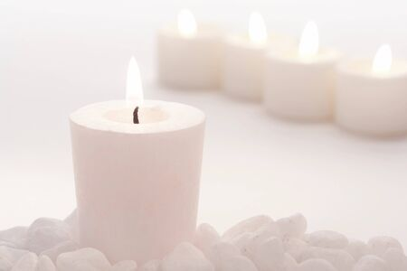 votive candle: Votive candle burning in a high key faded color setting in a spa