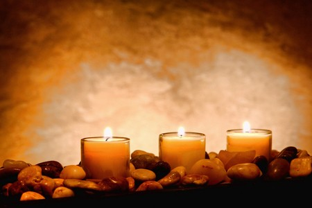 candles spa: Votive candles in glass holders on a bed of pebbles burning in a spa Stock Photo