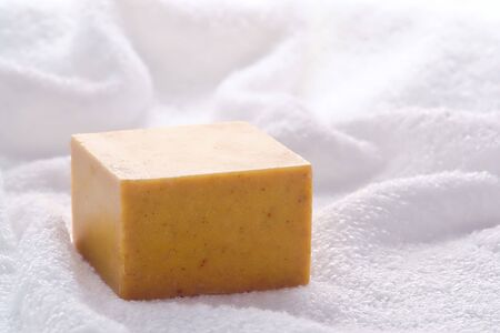 Block style bar of natural artisan aromatherapy soap on a fluffy white bath towel Stock Photo - 7298510