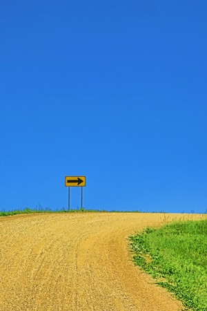 Sharp turn on a rural dirt gravel road with arrow warning sign photo