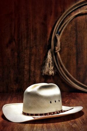 rodeo americano: Sombrero de vaquero blanco de rodeo oeste americano y auténtico lazo occidental colgado en una pared de madera en un granero ganadera