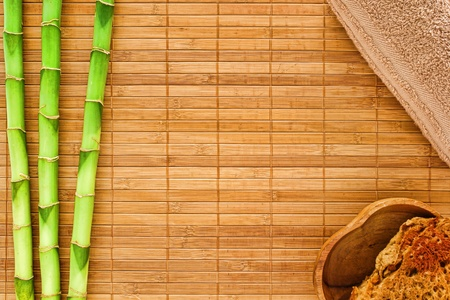 Natural spa background framed by green bamboo stems over brown mat with cotton towel and natural bath sponge in a wood bowl in corners photo