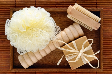 massager: Natural body care accessories gift kit with block style bar aromatherapy organic soap and loofah scrub sponge with foot massager and soft brush in a wood tray for a pampering holistic hygiene bath treatment in a naturalist spa in earthy brown colors Stock Photo