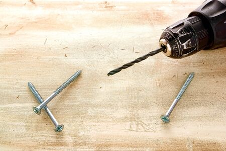 tool chuck: Boring bit mounted on a well worn chuck of a used drill tool and new Philips wood screws on grunge wooden surface in a woodworking carpentry workshop