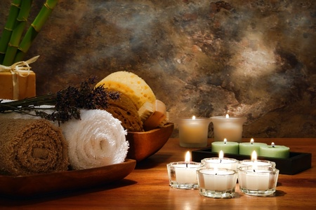 Aromatherapy votive candles burning with a soft glowing flame with towels and wellness treatment accessories in a spa