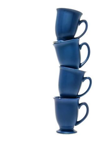 Blue ceramic coffee mugs stacked high as a column in a precarious balancing act over white