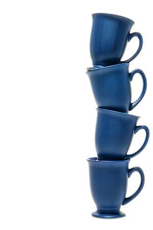 kockázatos: Kék kerámia kávéscsészék halmozott magas, mint egy oszlop a bizonytalan egyensúlyozás, felett, fehér