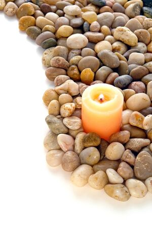 Votive candle burning with a soft glow flame in a bed of small polished pebble rocks over white