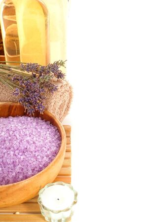 salts: Scented purple bats salts in a wood bowl and lavender flowers with cleansing hygiene accessories on a towel for a relaxing and pampering aromatherapy wellness session in a holistic relaxation spa
