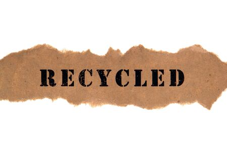 The environmentally correct title word recycled typed on a piece of eco friendly natural fiber content unbleached recycle style brown torn paper banner over white Stock Photo - 10136603