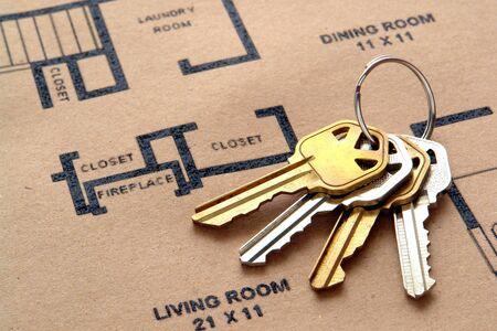 Klucze: Zestaw kluczy domowych w kółko nad prawdziwym domu nieruchomości budowlanych budowniczy planu architektonicznego podłogi wydrukowanej na brązowym papierze z odzysku