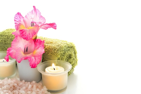 softly: Pink gladiolus flowers and softly burning aromatherapy candles with soft green towel over scented bath salts for a relaxing and pampering wellness session in a holistic relaxation spa Stock Photo