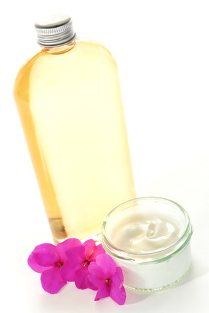 White facial care treatment cream in cosmetic glass jar and bottle of aromatherapy body oil with pink flowers for a soothing and relaxing holistic session in a spa Stock Photo
