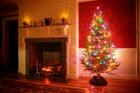 Christmas tree with vintage multi color lights in an old fashioned traditional interior with brick fireplace and warm burning fire log in hearth