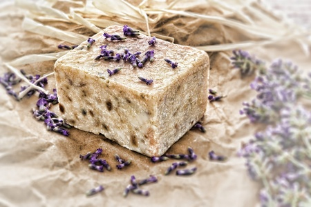 Traditional block style bar of scented natural artisan aromatherapy soap with fresh lavender flowers and seeds over old fashioned craft paper gift wrapping
