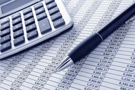 Ballpoint ink pen and calculator on a financial spreadsheet statement with columns of numbers for an accounting budget finance reconciliation photo