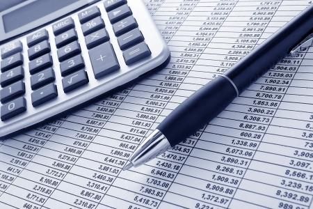 hoja de calculo: Bol�grafo de tinta de bol�grafo y calculadora en un comunicado de hojas de c�lculo financieras, con columnas de n�meros para una conciliaci�n contable financiar el presupuesto Foto de archivo