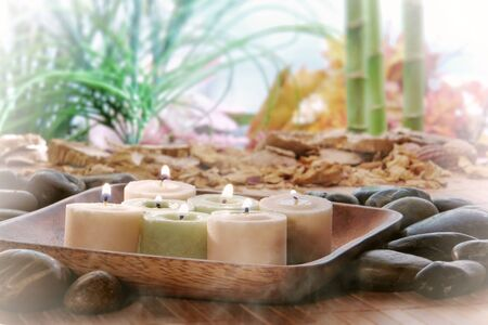 votive: Votive candles burning with a soft glowing flame in a wood dish in a natural exotic environment with smoke haze over a lush tropical vegetation background during a spiritual Zen meditation session