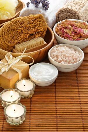 Complete experience kit of total body care accessories and cosmetics items for a pampering aromatherapy and wellness relaxation session in a spa with natural body scrub sponge, bath salts, facial cream, nail brush, artisan bar soap, dried flower petals, m Stock Photo - 10180496
