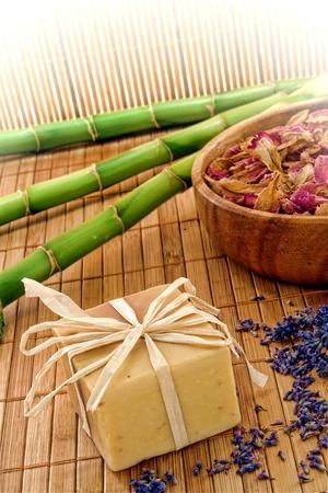 flores secas: Aromaterapia artesanal natural, artesanía hecha de barras de jabón estilo bloque con flores secas pétalos en un tazón de madera y semillas de lavanda en una estera de bambú en un spa