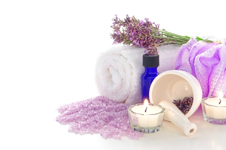 Aromatherapy treatment kit with fresh lavender flowers, aromatic scented purple bath salts, soft white towel, burning candles, mortar with natural seeds, scrub wash mesh cloth and essential oil bottle for a relaxing body care session in a spa