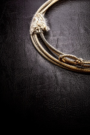 American West authentic vintage rodeo cowboy lariat lasso on grunge black leather surface background photo