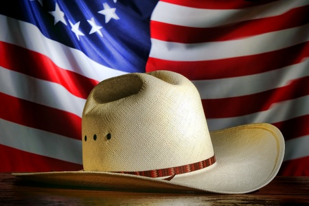 western usa: American West rodeo cowboy traditional white straw hat over waving old and antique historic US flag at a patriotic Western event Stock Photo