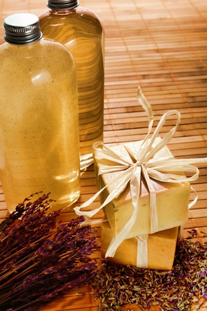 Natural artisan made aromatherapy scent bath soap bar and cosmetics body care wash and scrub bottles with lavender flower bunch and loose spread seeds in a spa Imagens