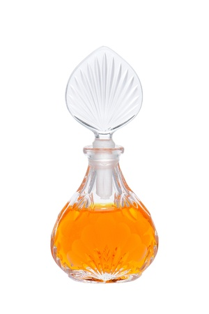 perfume bottle: Antique cut glass cosmetic bottle of perfume with orange scented liquid fragrance isolated on white Stock Photo