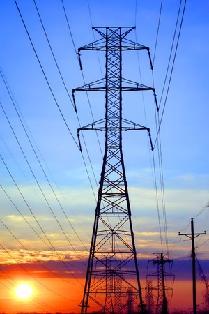 electric grid: Electric grid network power high voltage transmission lines pylon tower and electrical wires at sunset