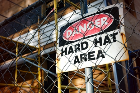 Danger hard hat area safety warning sign on a chain link fence at a house construction work site  Imagens
