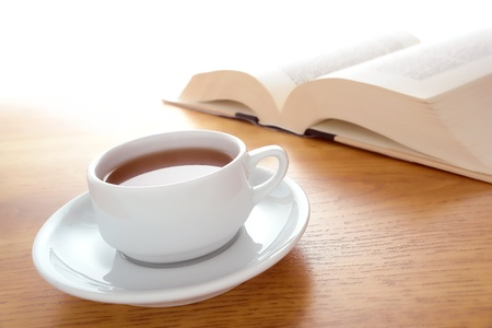 Cup of coffee or tea and big book open on a table for relaxing reading leisure time Banco de Imagens