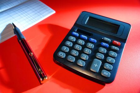 Calculator with ballpoint pen on a bank account checkbook register on red surface