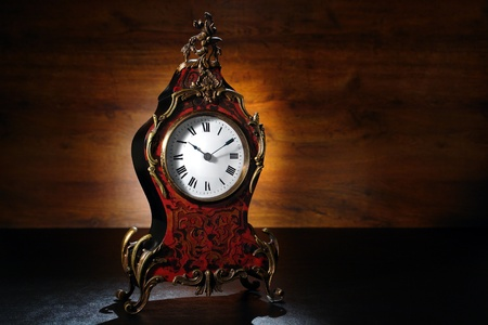 surmounted: Classic tortoiseshell inlaid and ornamental brass antique French period mantle clock with roman numerals and case of waisted form surmounted by gilt bronze