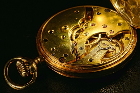 plated: Antique gold plated pocket watch with open interior showing mechanical movement with adjustable speed regulator above balance wheel in motion and ruby jewels  Stock Photo