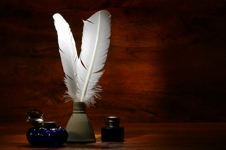 ceramic bottle: Old fashioned ink writing feather quills in antique ceramic inkwell with old, blue glass ink jars with silver lids