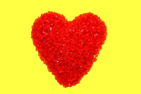 Symbolic heart shape made of a pile of red crushed glass pieces over bright fluorescent yellow background