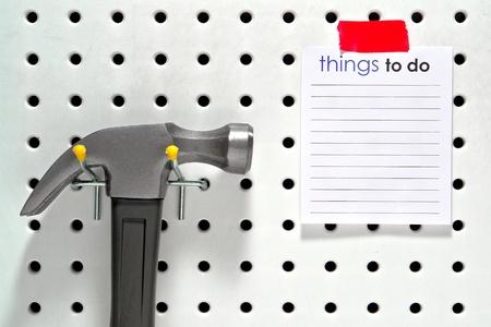 便利屋ものリストに空白のメモ帳にプロジェクトに掛かる建設ハンマーが付いている家のワーク ショップ ツール ハンガー ボード上でテキストの挿 写真素材