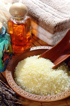 Natural aromatic sea bath salts and scooper in a wood bowl dish with aromatic liquid soap bottles and towels in an aromatherapy spa