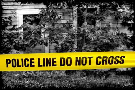 escena del crimen: L�nea de polic�a no cruzan cinta de advertencia amarilla delante de casa grunge blanco y negro de horror acordonada como una escena de crimen espantoso  Foto de archivo
