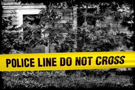 police tape: Police line do not cross yellow warning tape in front of grunge black and white house of horror cordoned off as a gruesome crime scene  Stock Photo