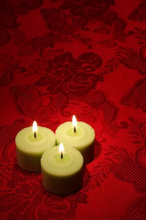Green decorative wax candles burning with a soft glowing flame on a red damask fabric background