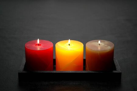 Elegant red yellow and green decorative marbleized pillar candles burning with a soft glow flame in a tray on sophisticated black Imagens