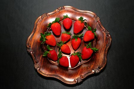 Fresh ripe red strawberries fruits in a classic and elegant antique wood serving tray on sophisticated black leathery surface