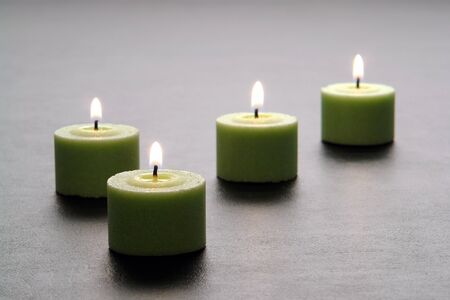 leathery: Green decorative votive wax candles burning with a soft glowing flame on an elegant black leathery surface  Stock Photo