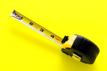 inches: Self retracting construction tape measure tool with floating tang and foot and inches markings on bright safety yellow background Stock Photo