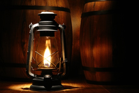 wood burning: Old-fashioned black kerosene oil lantern light with intense glowing flame burning near old distressed aged wood barrels in an Western antique ranch warehouse Stock Photo