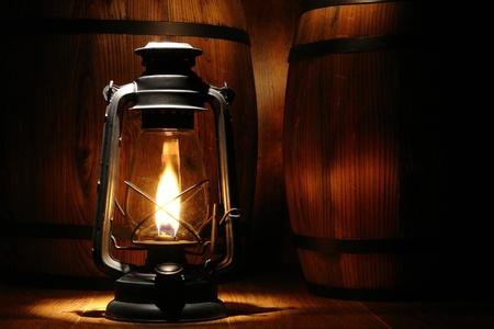 kerosene: Old-fashioned black kerosene oil lantern light with intense glowing flame burning near old distressed aged wood barrels in an Western antique ranch warehouse Stock Photo