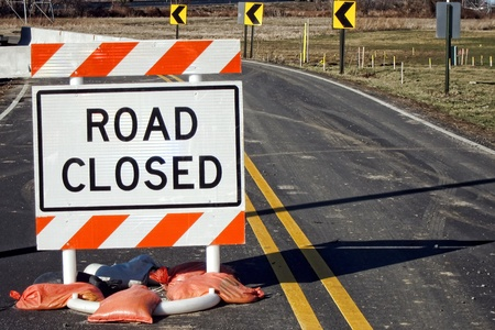 Road closed warning traffic safety sign on a small two lane country road under improvement  construction repair Stock Photo - 10262644
