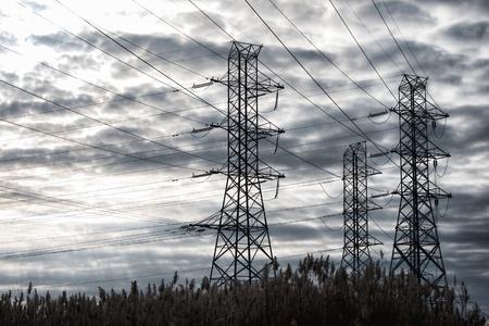 torres de alta tension: De alta tensión eléctrica las líneas de transmisión de energía en las torres por encima de una torre de carrizos más dramático, cielo, nubes de tormenta Foto de archivo